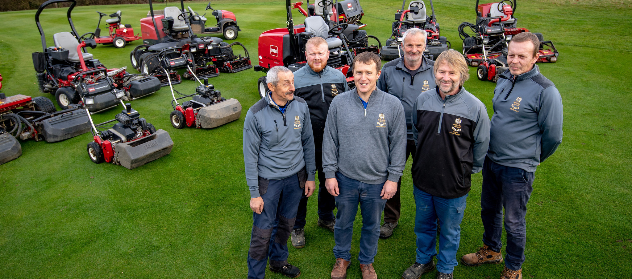 greenkeepers stood with equipment