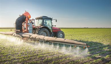 Red Tractor Spraying Field With Boom Sprayer